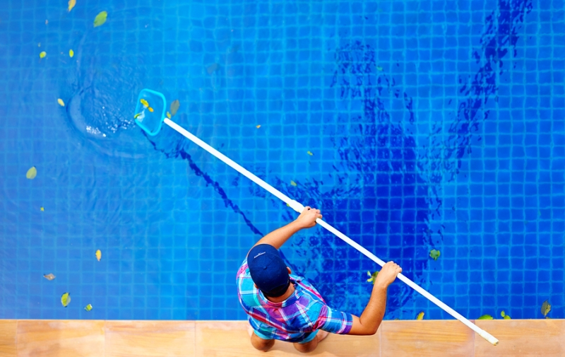 A pool cleaning professional cleaning a swimming pool