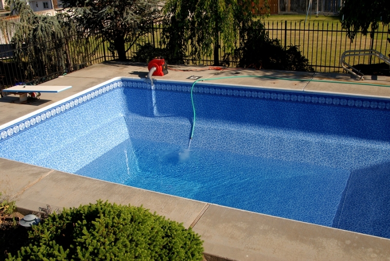 A swimming pool with a new pool liner being filled with water