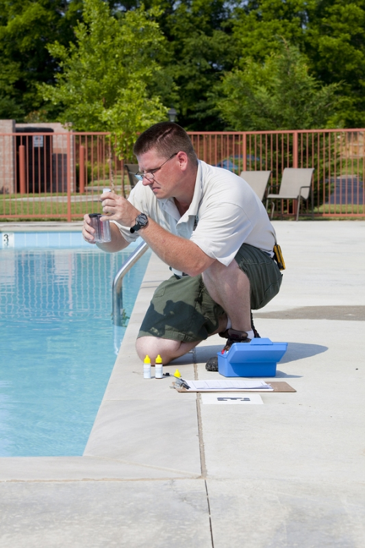 A pool service professional conducting pool chemistry test