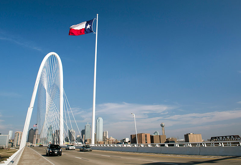 The Margaret Hunt Hill Bridge in Dallas, TX with the Texas flag flowing in front of the skyline.