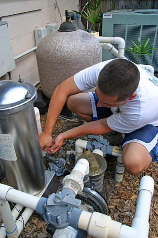 a service man kneels between the pipes of a pool pump